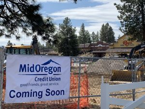 Construction Begins On New Sisters Location for Mid Oregon | Mid Oregon banner on fence with construction and Rays Food Place in the background.